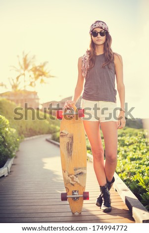 Beautiful hipster girl with skateboard, backlit at sunset - stock photo