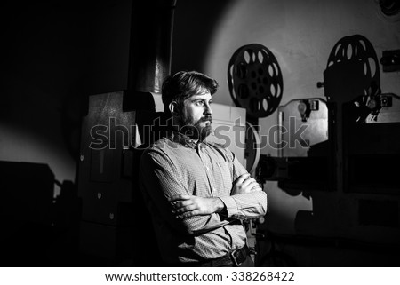 beautiful hipster man standing near a film projector in the room projectionist - stock photo