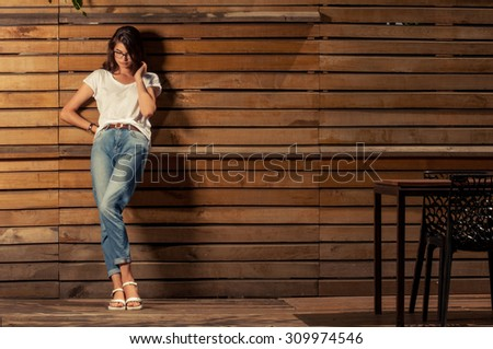 Beautiful hipster woman leaning on wooden fence wearing white t-shirt and jeans - stock photo