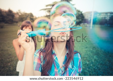 beautiful hipster young women sisters friends blowing bubbles in the city - stock photo