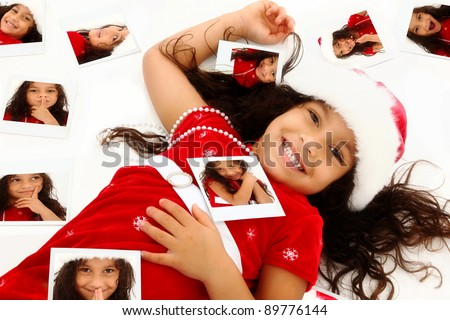 Beautiful Hispanic African American Girl Child in Santa Hat Christmas Dress surrounded by self instant photo portraits on floor. - stock photo