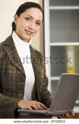 Beautiful Hispanic business lady is working on her notebook - stock photo