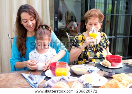 Beautiful hispanic family having breakfast together on the outdoor dining showing family bonding time. Focus is on child learning to drink milk. - stock photo