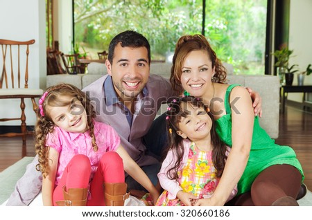 Beautiful hispanic family of four sitting on floor of livingroom posing happily for camera. - stock photo