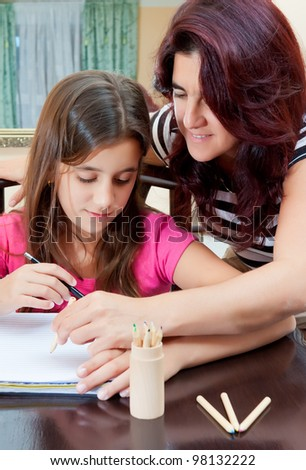 Beautiful hispanic girl and her young mother  studying at home