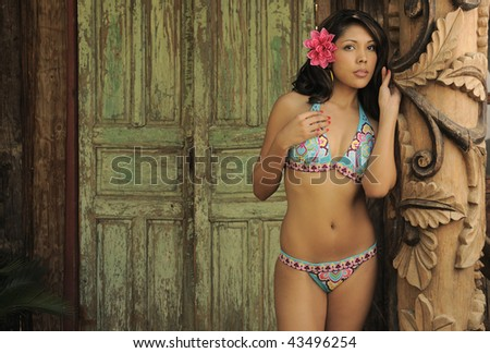 Beautiful Hispanic model with flower in her hair leaning against carved post in front of green weathered door. - stock photo