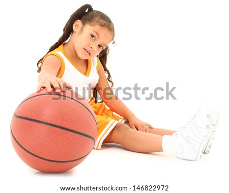 Beautiful Hispanic preschool girl with basketball in uniform. clipping path - stock photo