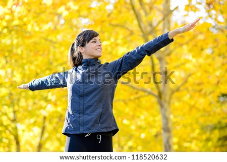 Beautiful hispanic sportswoman doing aerobic and pilates exercising outdoor. Arms raised in cross. Autumn blur golden leaves on background. - stock photo