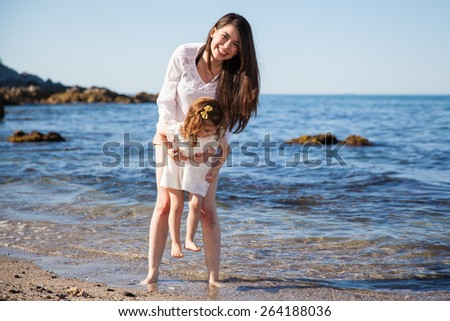 Beautiful Hispanic woman and her daughter having fun and laughing together at the beach on a sunny day
