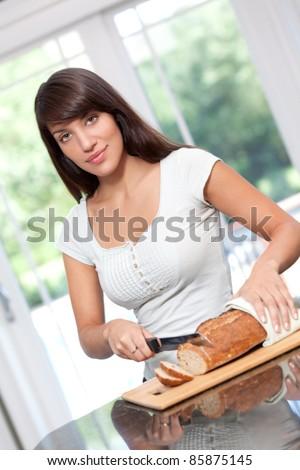 Beautiful hispanic woman cutting bread - stock photo
