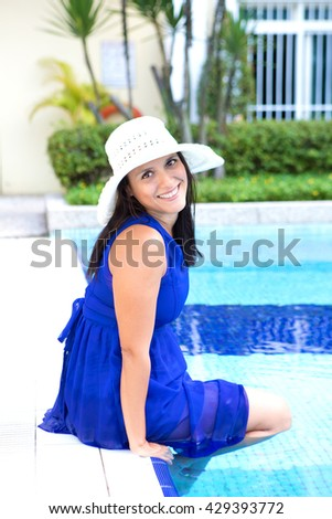 Beautiful hispanic woman in blue dress by the swimming pool - stock photo