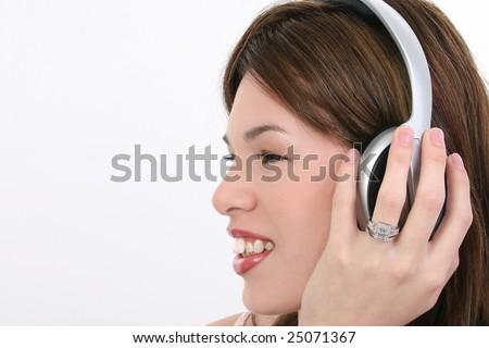 Beautiful Hispanic woman listening to audio over headphones. - stock photo