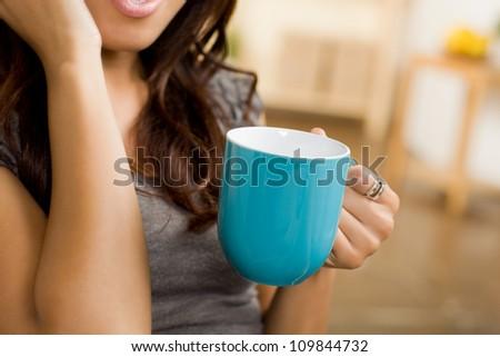Beautiful Hispanic woman relaxing at home wearing short sleeve gray shirt and shorts. - stock photo