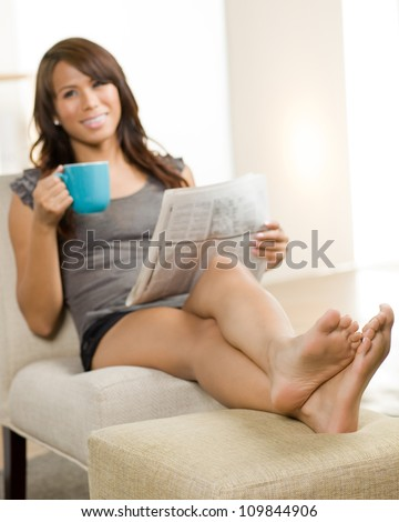 Beautiful Hispanic woman relaxing at home wearing short sleeve gray shirt and shorts.