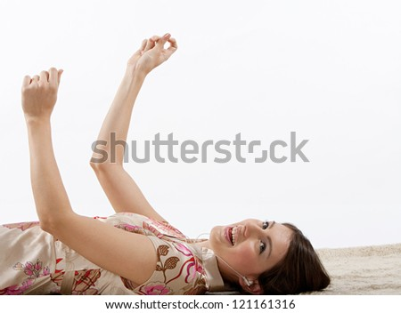 Beautiful hispanic young woman laying down on a furry carpet at home, listening to music with her earphones and clicking her fingers following the rhythm and singing along. - stock photo