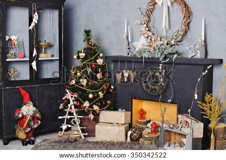 Beautiful holiday decorated room with Christmas tree with presents under it. Fireplace with beautiful Christmas decorations in comfortable living room. - stock photo
