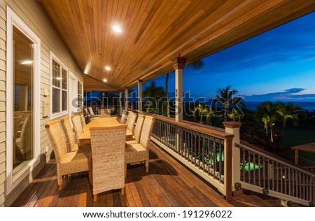 Beautiful Home Exterior Patio Deck and Dining Table with Sunset View - stock photo