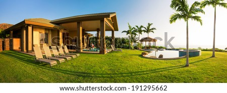 Beautiful home with large grassy green lawn and pool - stock photo