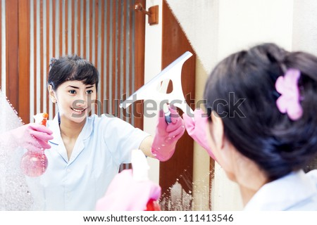 Beautiful Hotel maid wearing pink gloves cleaning up the mirror of bathroom - stock photo
