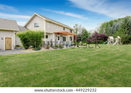 Beautiful house backyard with well kept lawn, patio area and playground at the background - stock photo