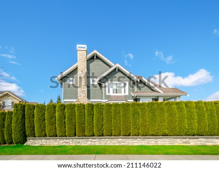Beautiful house behind green hedge fence. Landscape trimming design. House exterior. - stock photo