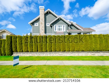 Beautiful house behind green hedge fence with empty for sale, lease, rent sign. Landscape trimming design. - stock photo