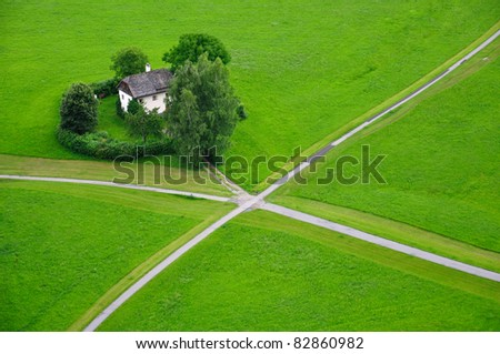 Beautiful house on a crossroads in a green field of Salzburg, Austria - stock photo