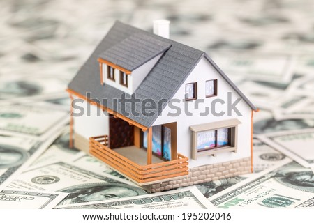 Beautiful house standing on 100 dollar bills. House expenses or investing concept. - stock photo
