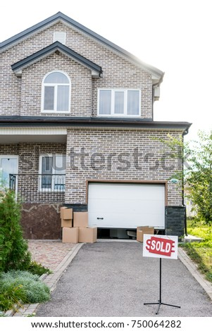 beautiful house with signboard sold and cardboard boxes