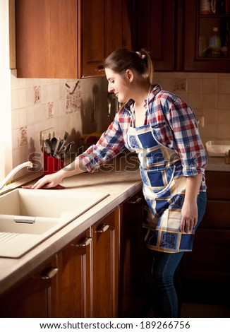 Beautiful housewife cleaning tabletop on kitchen - stock photo