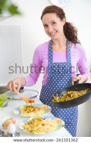 beautiful housewife cooked dinner in the kitchen - stock photo