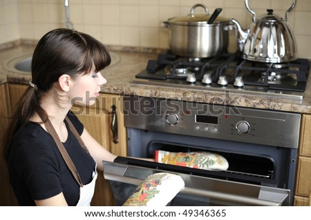 Beautiful housewife using the oven - stock photo