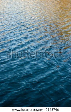 Beautiful hues of a fall sky reflected in water with small waves and ripple patterns.