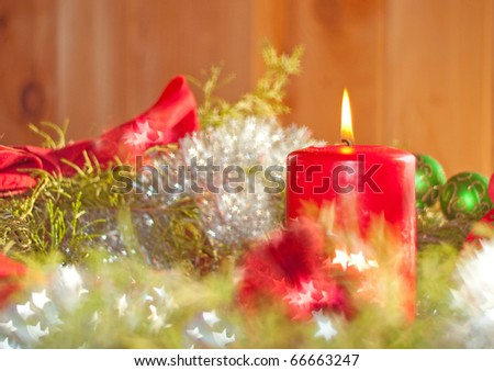 Beautiful image of a Christmas candle adorned by star bokeh reflecting off shiny decorations