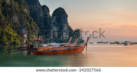 Beautiful image of sunset with colorful sky and Longtail boat on the sea tropical beach. Thailand - stock photo