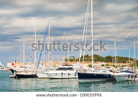Beautiful image of yachts against the backdrop of the city of St. Tropez in France. Interesting lighting accentuates the beauty of clouds azure shores.
