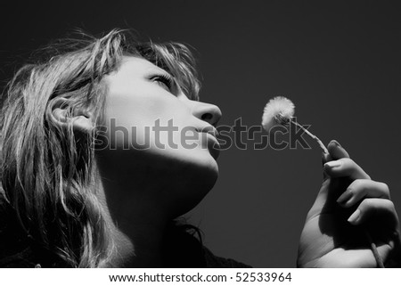 Beautiful image with a girl blowing dandelion's seeds