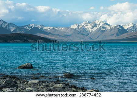 Beautiful incredibly blue lake Tekapo with  mountains, Southern Alps, on the other side. New Zealand - stock photo