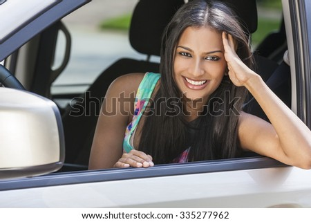 Beautiful Indian Asian young woman girl female driving a car - stock photo