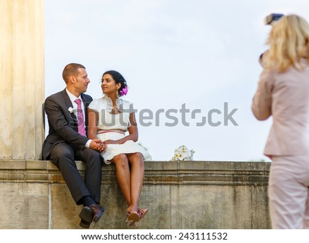 Beautiful indian bride and caucasian groom,  after wedding ceremony. Happy couple in love, celebrating wedding. Making photosession by photographer - stock photo