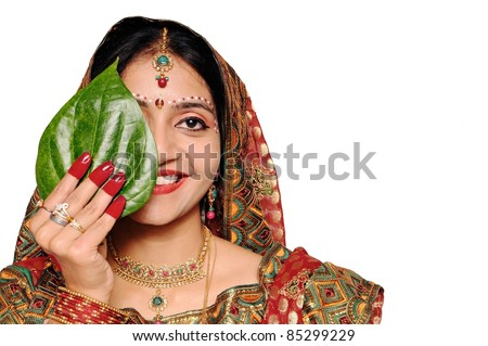 Beautiful Indian bride in red sari holding a green leaf. She looks stunning!!! - stock photo