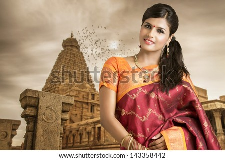 Beautiful Indian girl in traditional Indian sari on temple background ...
