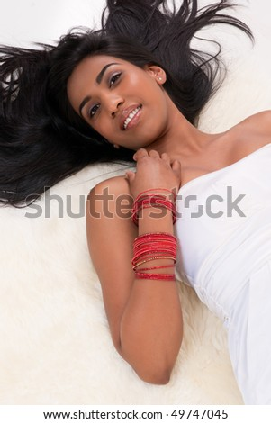 Beautiful Indian girl in white dress laying on cozy sheepskin