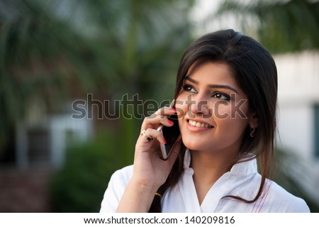 beautiful Indian girl talking over the phone in outdoor. - stock photo