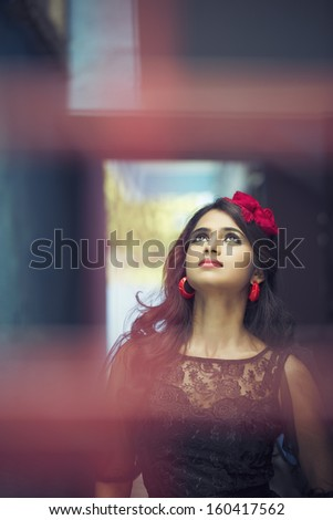 Beautiful Indian girl wearing Black Gown in outdoor background. - stock photo