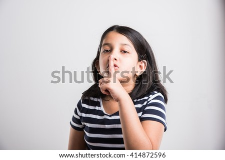 Beautiful indian little girl putting finger up to lips & ask silence onwhite background. asian girl child doing a Please Keep Quiet gesture towards the camera, indian small girl & silence please sign - stock photo