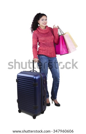 Beautiful indian tourist standing in the studio while wearing winter clothes and carrying luggage with shopping bags - stock photo
