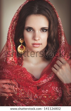 Beautiful indian woman bride bellydancer in traditional wear with bridal makeup and jewelry. gorgeous brunette traditionally dressed in India. Girl bollywood dancer in red Sari. Arabian bellydancer - stock photo