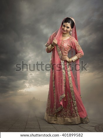 Beautiful Indian woman in glamorous outfit and jewelry with makeup in outdoor background. - stock photo