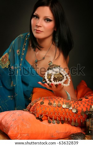 beautiful indian woman laying in ethnic interior